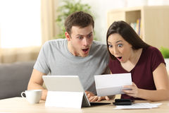 Amazed couple reading together a letter Royalty Free Stock Photography