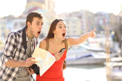 Amazed couple of tourists finding destination. Amazed couple of tourists finding location in a vacation travel with a port of a town in the background Stock Photography