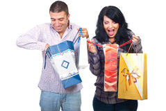 Amazed couple of what they bought. Amazed happy couple of what they bought looking in their shopping bags isolated on white background Stock Photography