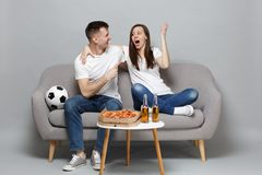 Amazed couple woman man football fans cheer up support favorite team expressive gesticulating hands, hugging isolated on. Amazed couple women men football fans royalty free stock image