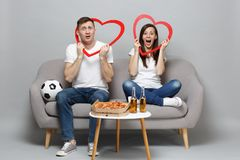 Amazed couple woman man football fans cheer up support favorite team, sitting holding big red wooden hearts isolated on. Amazed couple women men football fans royalty free stock photography