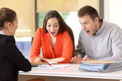 Amazed customers reading contract conditions. Two amazed customers reading contract conditions at office Stock Photo