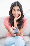 Amazed cute brunette sitting on couch holding remote. In bright living room Royalty Free Stock Photos