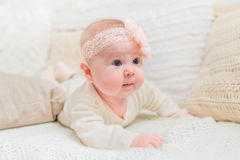 Amazed cute little baby with chubby cheeks wearing white clothes and pink band with flower lying on bed with knitted pillows Royalty Free Stock Images