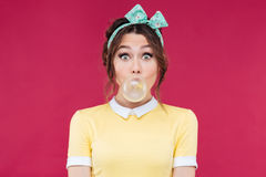 Amazed cute pinup girl blowing a bubble gum balloon Stock Photos