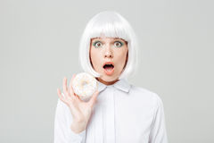 Amazed cute young woman in blonde wig holding donut. Over white background Stock Images