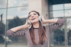 Amazed dreamy young lady is listening to her favourite song outs. Ide, walking on the spring street, wearing cozy clothes, modern big headphones, singing Royalty Free Stock Images