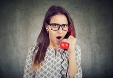 Amazed entsetzte die Frau, die an einem Telefon spricht stockfotos