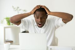 Amazed excited african-american man surprised by unexpected good. News win result online, astonished black businessman looking at laptop screen with wow face stock image
