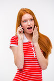 Amazed excited redhead woman talking on mobile phone Stock Photos