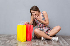 Amazed excited young woman looking into bags. Amazed excited surprised curious young woman sitting on the floor with crossed legs and looking into bags Royalty Free Stock Photo