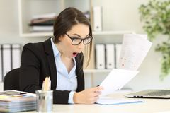 Amazed executive checking sales results at office Stock Image