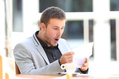 Amazed executive reading a letter in a bar. Portrait of an amazed executive reading a letter sitting in a coffee shop Royalty Free Stock Images