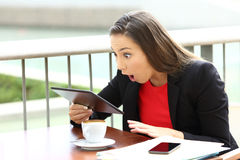 Amazed executive receiving good news in a tablet. Sitting in a coffee shop stock photos