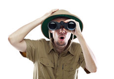 Amazed explorer looking through binoculars. Young man wearing safari shirt and pith helmet looking through binoculars with a surprised expression, isolated on Stock Photography