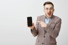 Amazed fascinou o homem bonito com a cerda nos vidros e no revestimento formal que sorri alegremente apontando no smartphone fotografia de stock royalty free