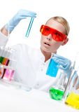 Amazed female doctor does experiment. Amazed female doctor in spectacles does some experiments, isolated on white Stock Photos