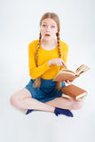 Amazed female student sitting on the floor with book Stock Photography