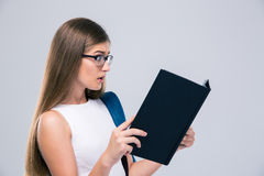 Amazed female teenager reading book Royalty Free Stock Photography