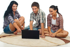 Amazed friends with laptop. Happy friends sitting on carpet and being amazed about laptop screen over white background Royalty Free Stock Photo