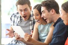 Amazed friends watching media in a tablet. Four amazed friends watching media content together in a tablet sitting on a sofa in the living room at home Royalty Free Stock Photo