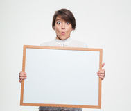 Amazed funny young woman holding blank board Stock Photo