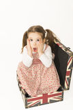 Amazed girl closeup portrait. Little girl standing in suitcase beeing surprised, isolated on white background Royalty Free Stock Photos