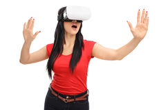Amazed girl experiencing virtual reality. Via VR goggles isolated on white background Stock Image