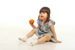 Amazed girl holding mandarin Royalty Free Stock Image