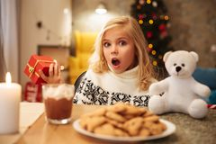 Amazed girl in knitted sweater holding gift box while sitting at. Festive table, looking at camera Stock Photos