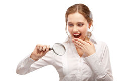 Amazed girl looks through magnifier Royalty Free Stock Photos