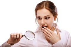Amazed girl looks through magnifier Royalty Free Stock Photo