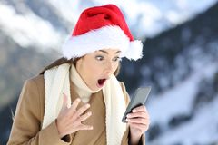 Amazed girl reading on line news in christmas. With a snowy mountain in the background Stock Photo