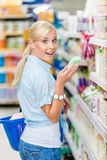 Amazed girl at the shop choosing cosmetics Royalty Free Stock Photography