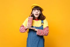 Amazed girl teenager in french beret, denim sundress holding plastic cup of cola or soda isolated on yellow wall. Background in studio. People sincere emotions royalty free stock photos