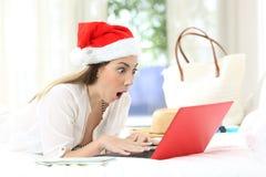 Amazed girl using a laptop on christmas holidays stock image