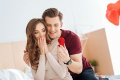 Amazed girlfriend looking at proposal ring held by boyfriend. Cannot believe my eyes. Surprised girl covering her mouth with hands while looking at a diamond stock photos
