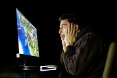 Amazed guy emotional playing computer game Stock Photo