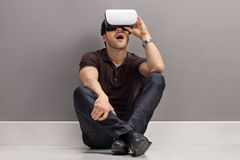 Amazed guy seated on the floor using a VR headset Stock Image