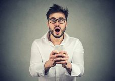 Amazed guy with smartphone looking stunned. Young handsome bearded man in shirt holding new smartphone and looking extra shocked at camera Stock Images