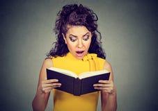 Amazed ha colpito la donna che legge un libro Fotografie Stock