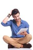 Amazed ha messo le buone notizie a sedere casuali della lettura dell'uomo sulla compressa Fotografia Stock Libera da Diritti