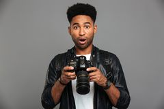 Amazed handsome afro american man in leather jacket holding digital camera stock photos