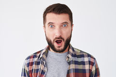 Amazed handsome man with beard looking at the camera. Close-up shot of amazed handsome man with beard looking at the camera over white background. Emotion Stock Photos