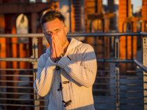 Amazed handsome man looking at camera outdoors. Man in white sweater covering mouth with hands and looking shocked at camera standing in sunlight on street royalty free stock photos