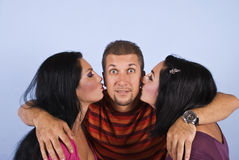Amazed happy man with kissing women. Amazed man with beard being kissed by two brunettes woman on blue background,check also Friends Royalty Free Stock Photo