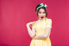 Amazed happy pinup girl in yellow dress. Standing and posing over pink background Stock Image
