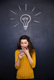 Amazed happy woman using mobile phone over chalkboard background Royalty Free Stock Image
