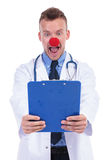 Amazed idiot doctor reading notes. Idiot doctor wearing a clowns red nose is amazed by the notes on his clipboard Stock Image