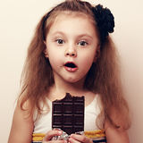 Amazed kid girl looking with open mouth holding chocolate. Close. Amazed kid girl looking with open mouth holding dark chocolate. Vintage closeup portrait Stock Photography